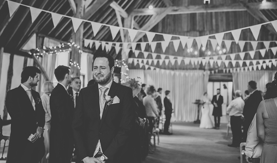 The groom gets emotional as he awaits the entrance of his beautiful bride at this barn wedding in Hampshire
