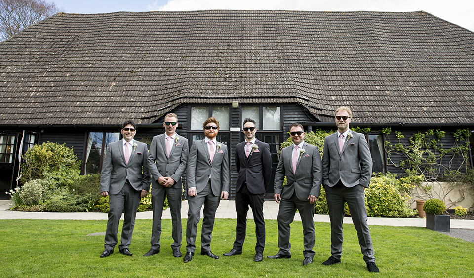 The groom and his groomsmen strike a pose before the wedding ceremony at Clock Barn in Hampshire