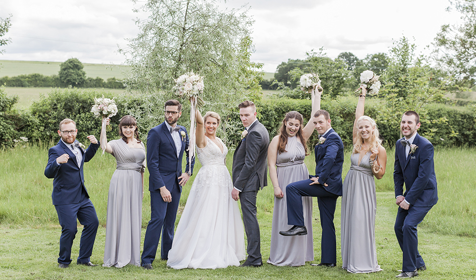 The bride and groom strike a pose with the groomsmen and bridesmaids at this barn wedding venue in Hampshire