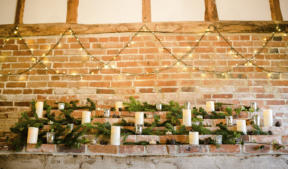 Decorate mantlepieces with lots of led pillar candles and seasonal firs and pine cones for a wonderfully rustic feel to your winter barn wedding at Clock Barn