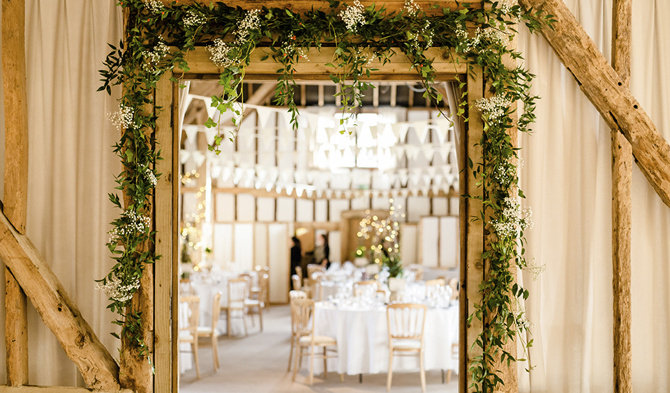 Decorate the entrance to the barn with garlands of pretty white gypsophila at your winter wedding at Clock Barn in Hampshire