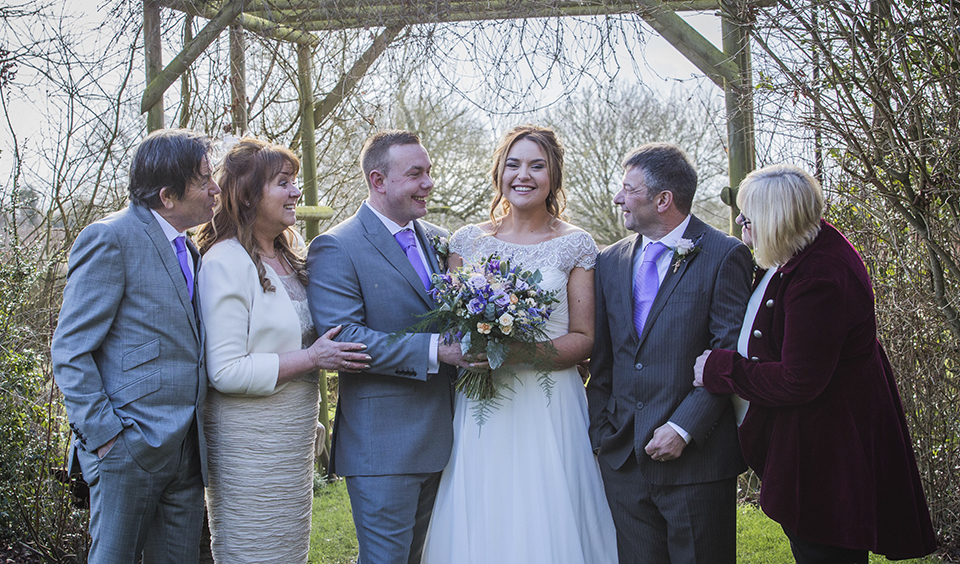 The happy couple pose for a photo with their parents in the garden at their spring wedding at Clock Barn in Hampshire