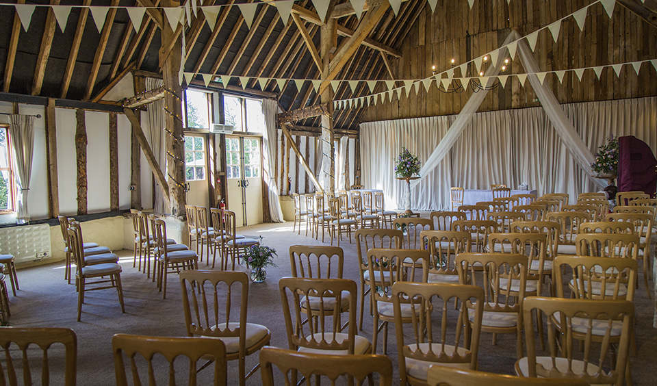 The barn is set up for the wedding ceremony and decorated with fairy lights and pretty white bunting at Clock Barn in Hampshire