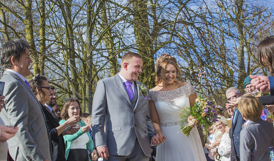 The wedding guests throw confetti over the happy newlyweds at their sunny spring wedding at Clock Barn in Hampshire