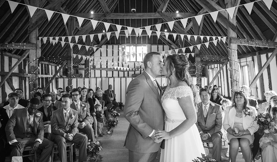 The happy newlyweds share their first kiss at their wedding ceremony at Clock Barn in Hampshire