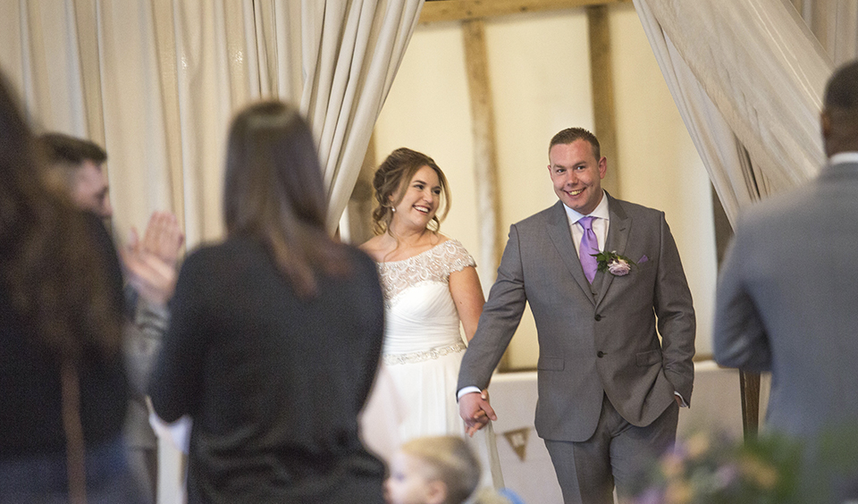 The happy newlyweds make a grand entrance to the wedding breakfast as their guests congratulate them at Clock Barn