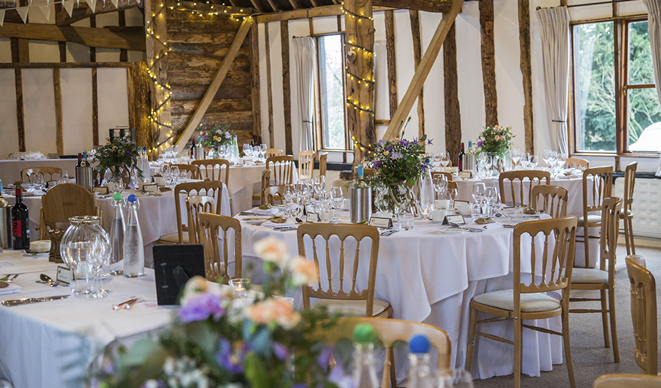 The barn at Clock Barn is set up for the wedding breakfast with vases of pretty spring flowers and tea lights as table centrepieces