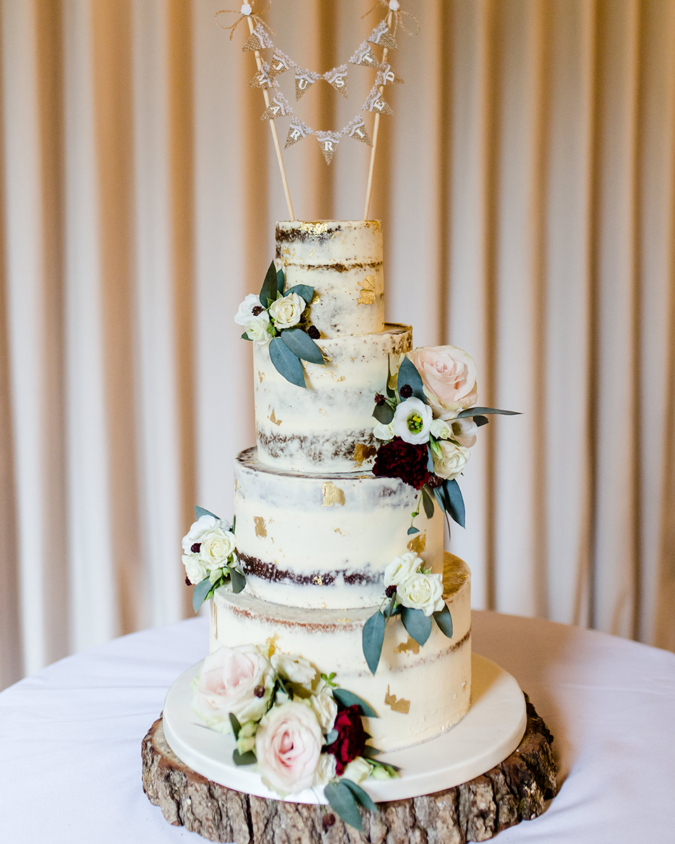 The wedding cake was 4 tiers of semi-naked cakes decorated with pretty flowers and displayed on a rustic log slice at Clock Barn