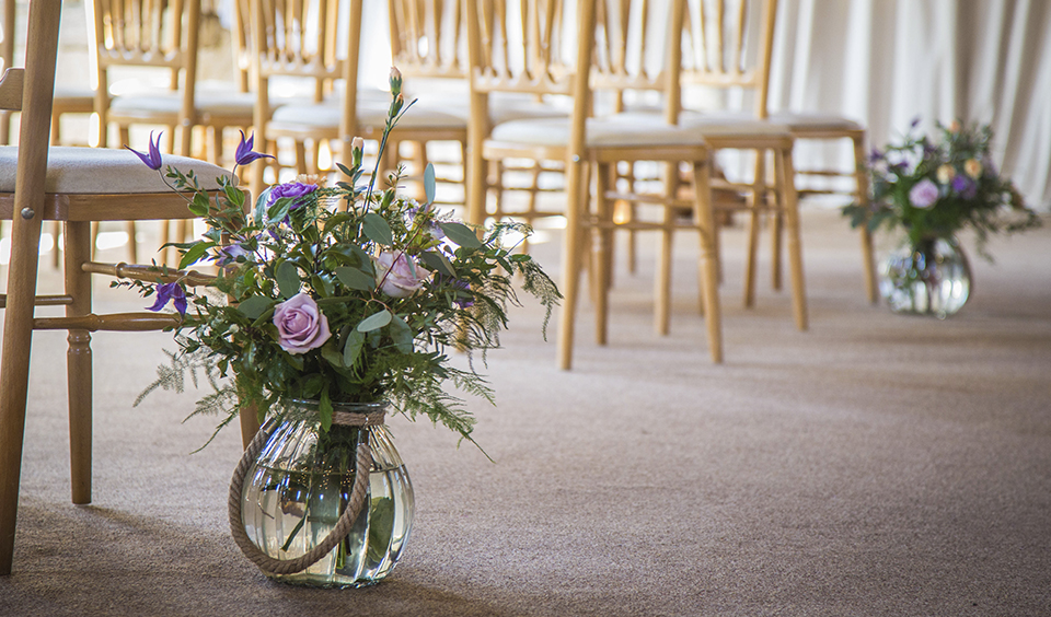 Beautiful spring blooms in vases decorated the wedding aisle at this barn wedding in Hampshire