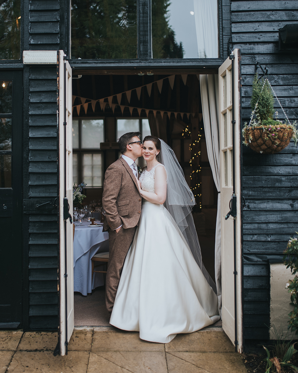 The happy newlyweds pose for a photo in the door way to the barn at Clock Barn in Hampshire