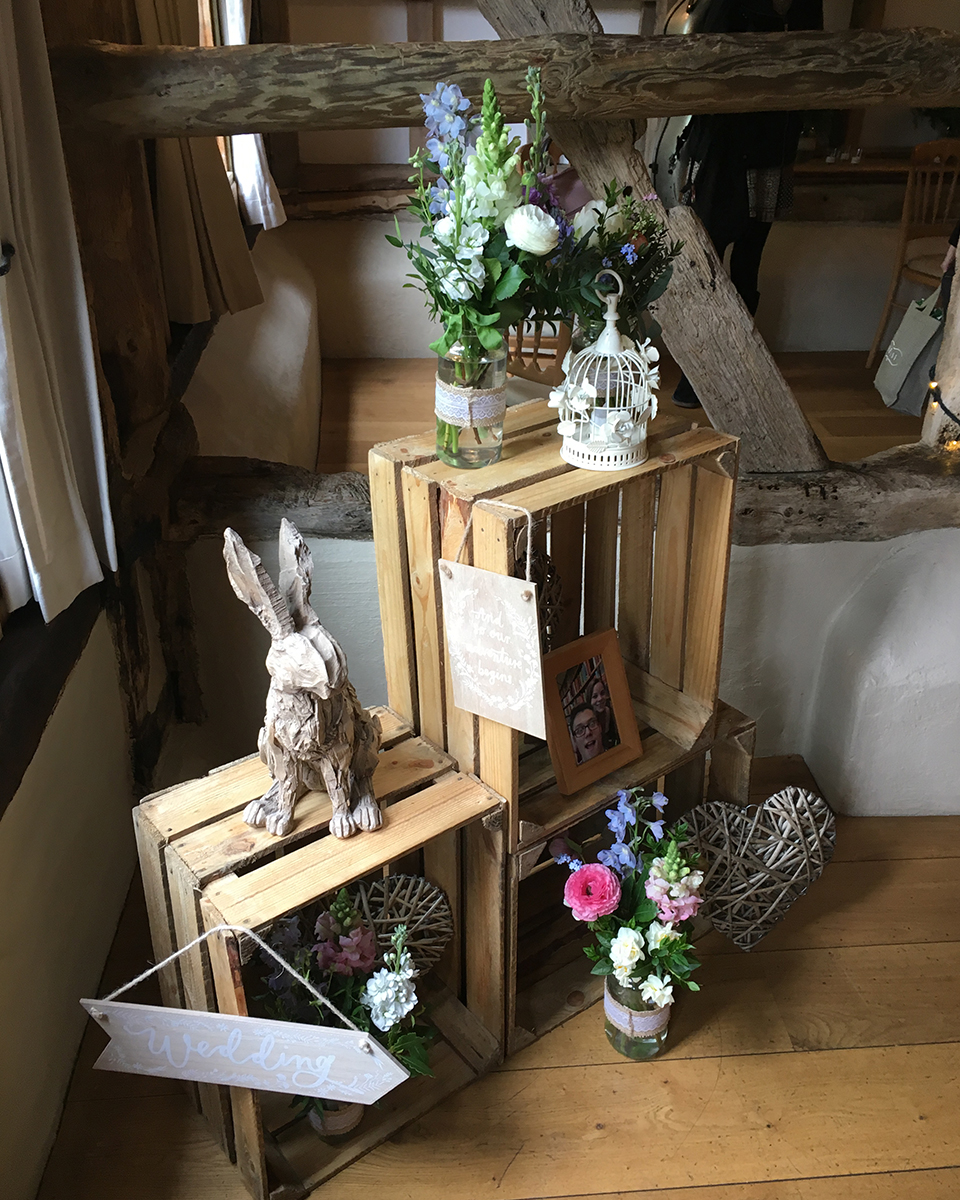 Wooden crates were used to display wedding decorations at this rustic barn wedding in Hampshire