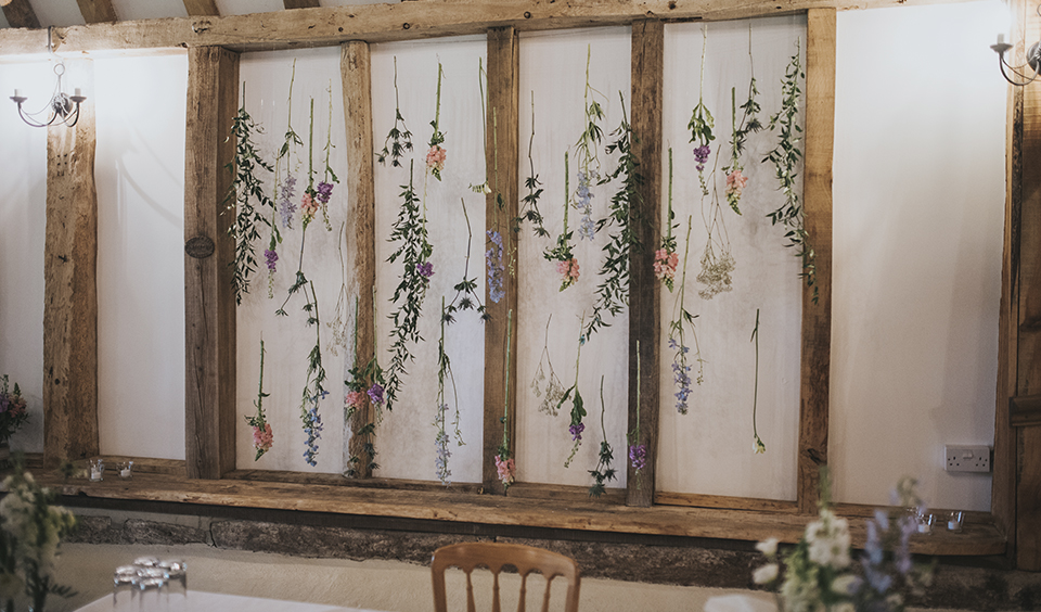 Delicate spring flowers were hung from the beams at this rustic wedding at Clock Barn in Hampshire