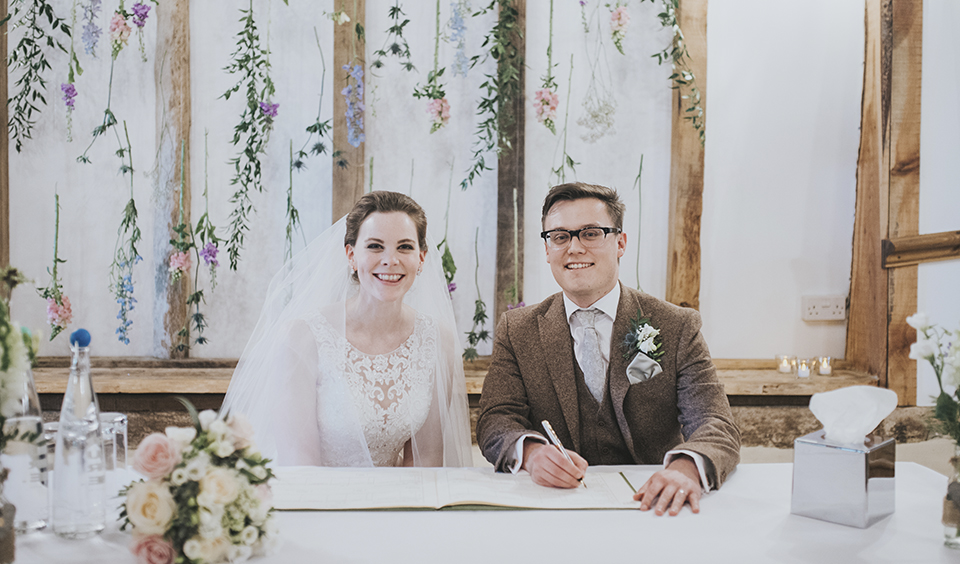 The happy newlyweds sign the register at their wedding at rural wedding venue Clock Barn