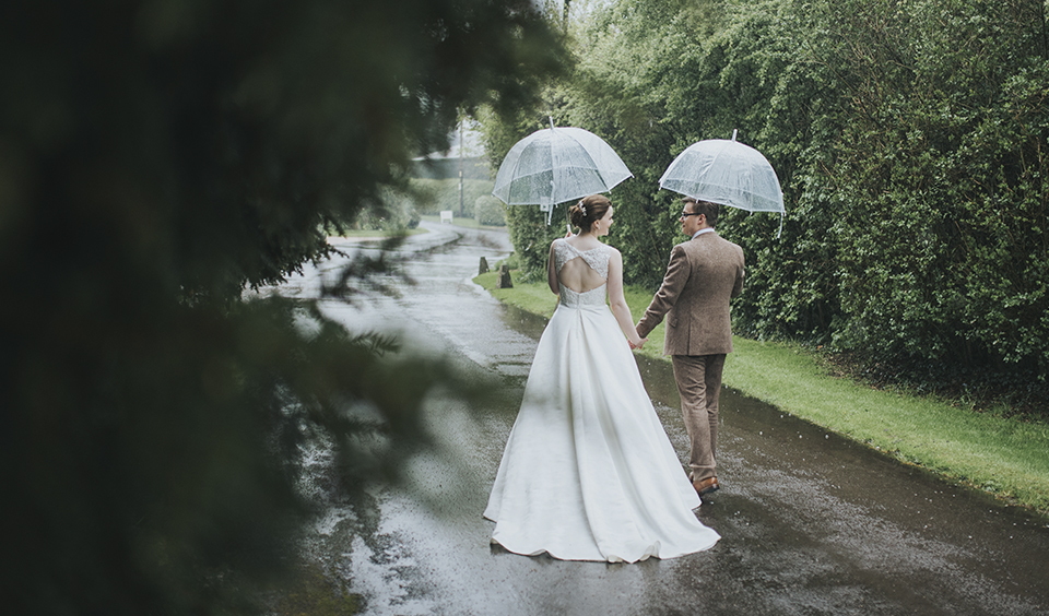 The bride and groom brave the elements to have some wedding photos taken at rural wedding venue Clock Barn