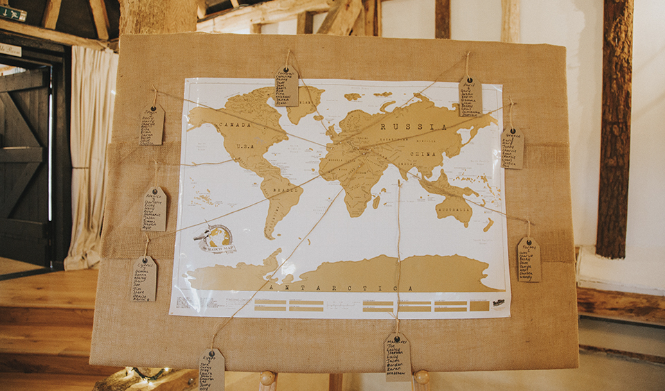 The wedding couple chose a map of the world labelled with the places they had travelled to as their table plan at Clock Barn