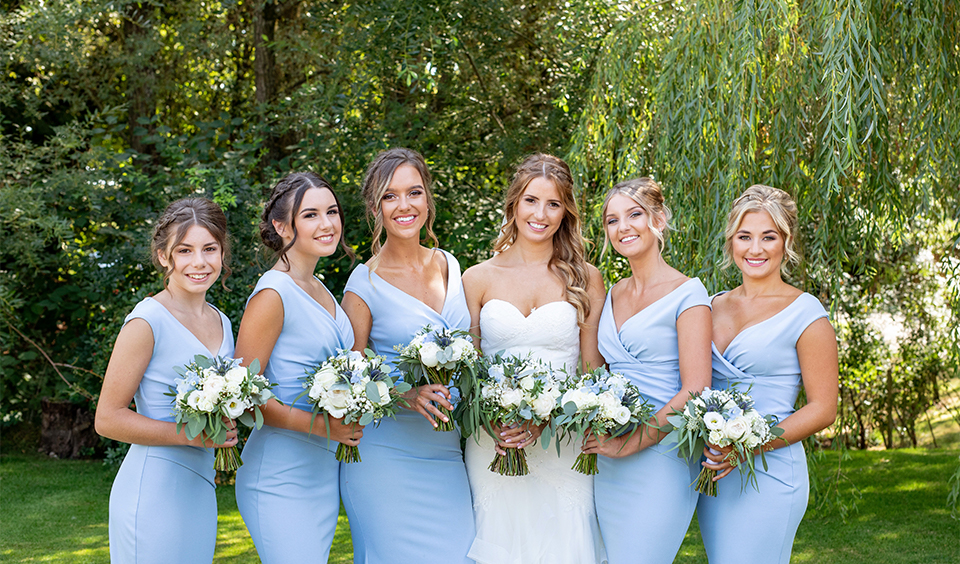 The bridesmaids wore pretty pastel blue bridesmaids dresses at this Clock Barn wedding.