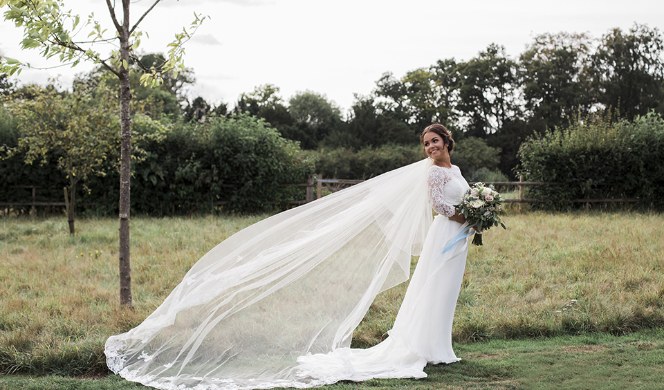 This long sleeved wedding dress with a cathedral length veil is a great choice for the chillier months of the year