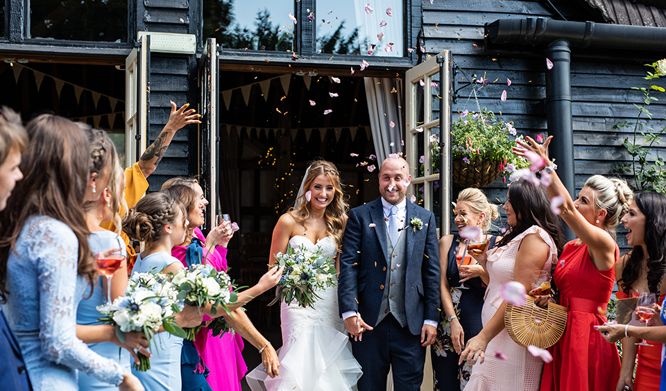 The happy newlyweds have confetti thrown over them by their wedding guests at their rustic barn wedding in Hampshire
