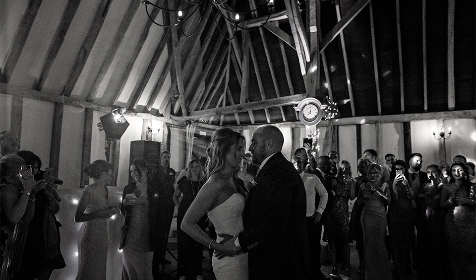 The happy newlyweds take to the dance floor for their first dance as their guests watch on at Clock Barn