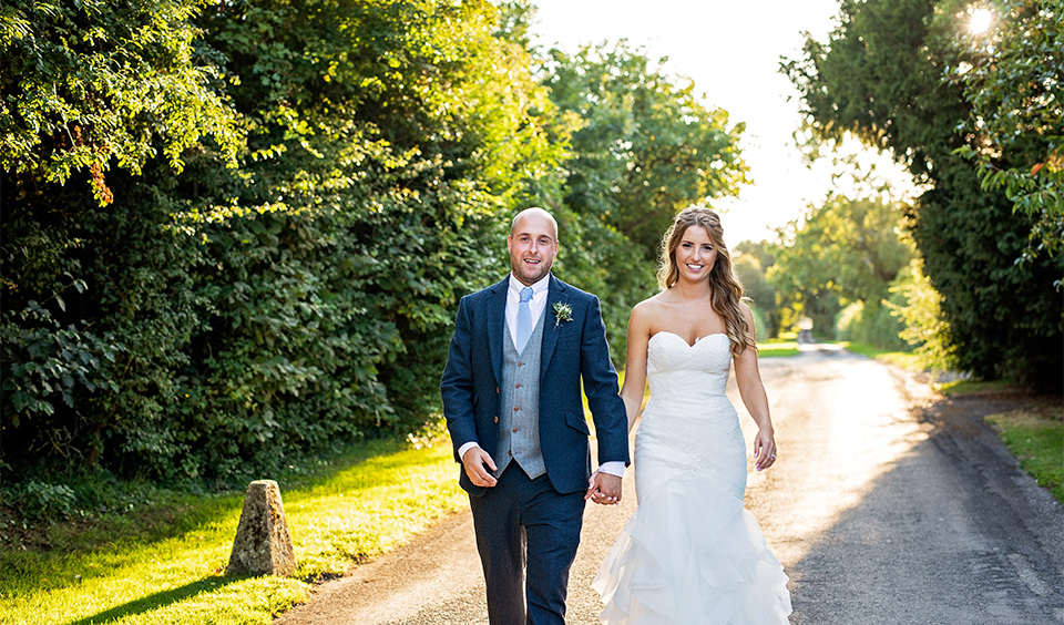 The happy couple take a stroll down the drive at their rural wedding in Hampshire