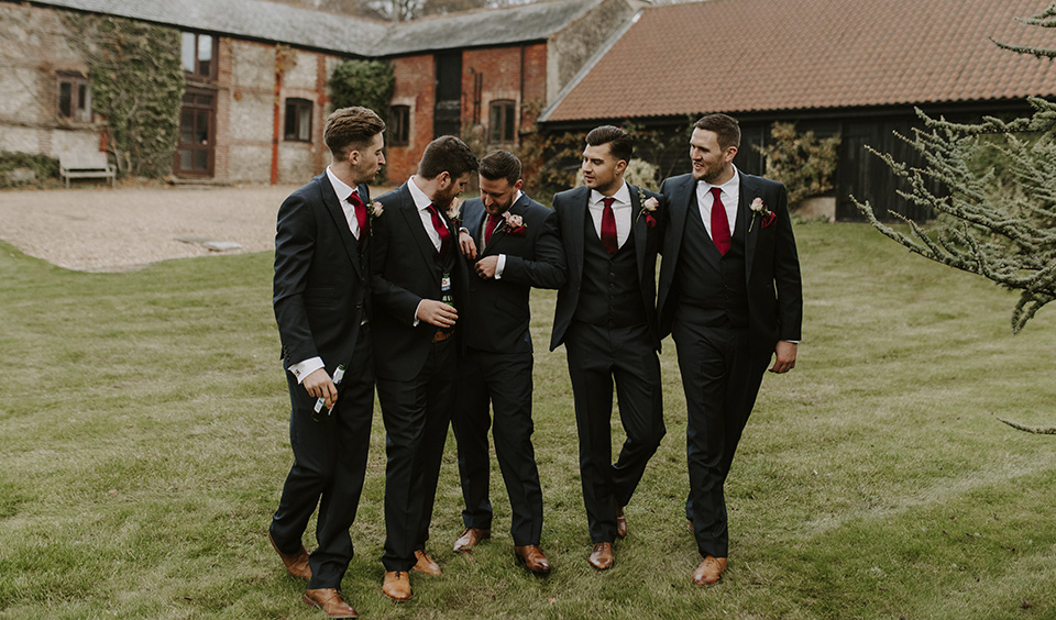 The groom and groomsmen looked the part in navy three-piece suits and claret ties at this winter wedding at Clock Barn in Hampshire