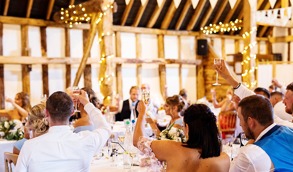 The wedding guests raise a glass to the happy couple at this rustic wedding venue in Hampshire