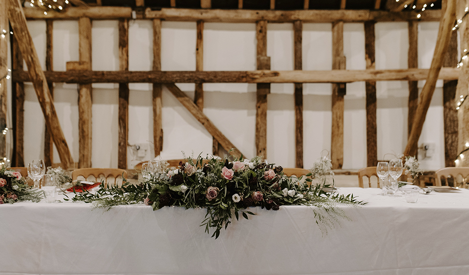 The top table was decorated with an arrangement of blush pink wedding flowers and lush foliage