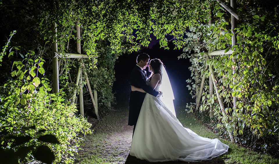 The bride and groom pose for an evening wedding photo in the gardens at Clock Barn