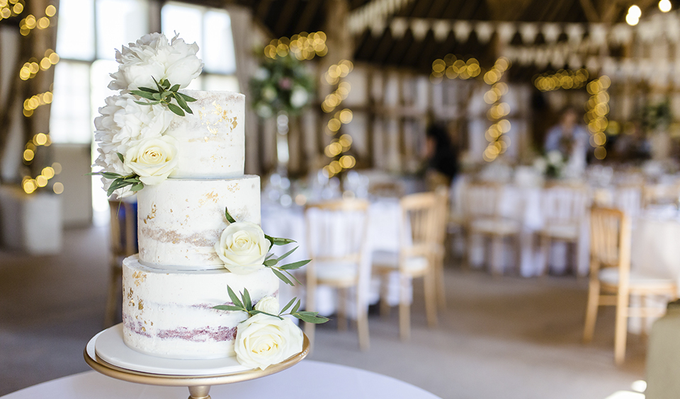 This three tier semi naked wedding cake has been decorated with gold leaf at this wedding at Clock Barn in Hampshire