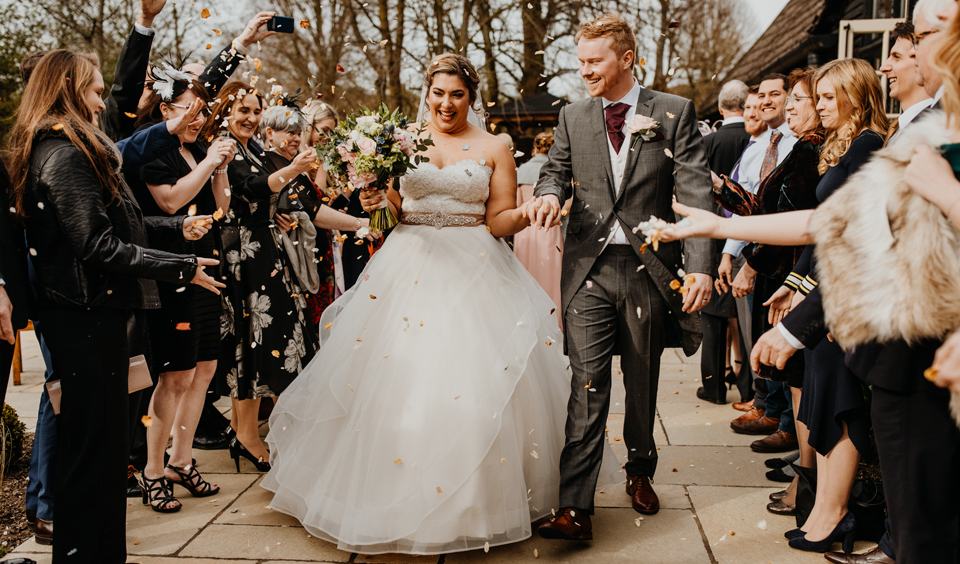 The bride and groom have confetti thrown over them following their wedding ceremony at Clock Barn
