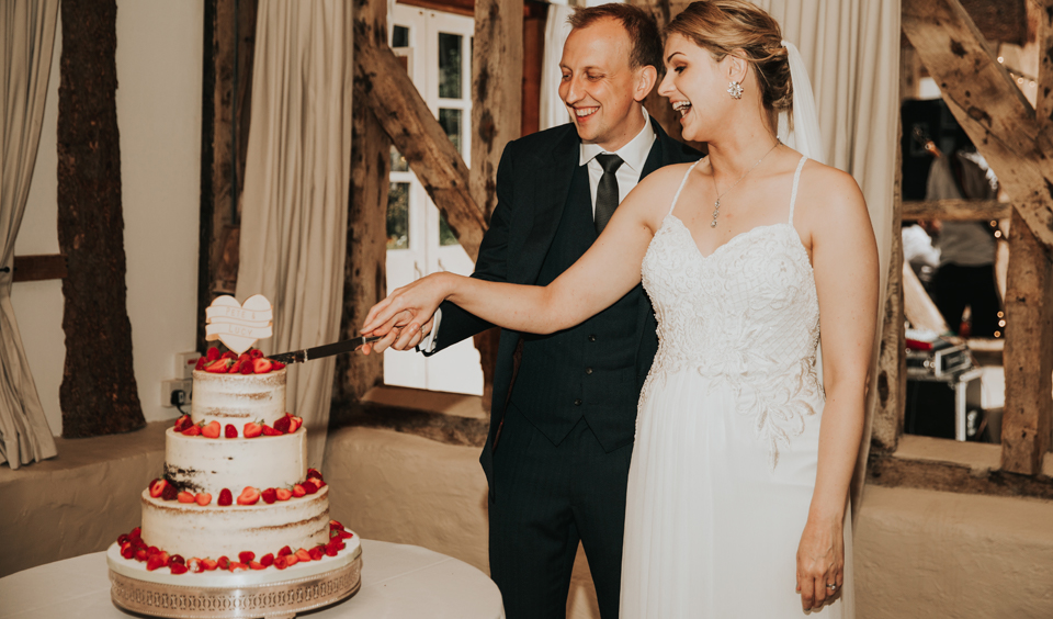 Bride and groom cutting the wedding cake at Clock Barn in Hampshire