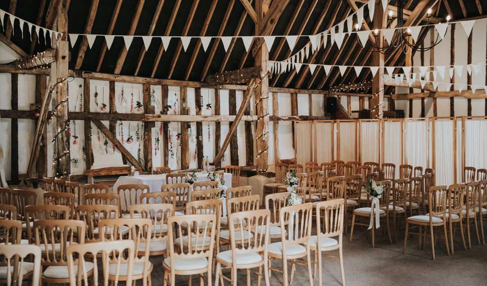 The barn is set up for the wedding ceremony at Clock Barn in Hampshire