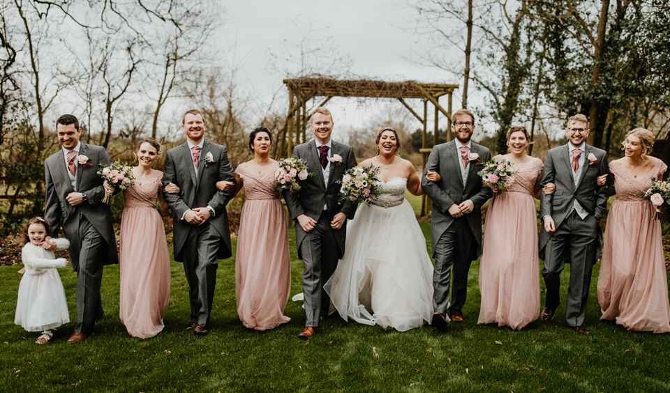 The bridal party pose for a wedding photo in the gardens at Clock Barn in Hampshire