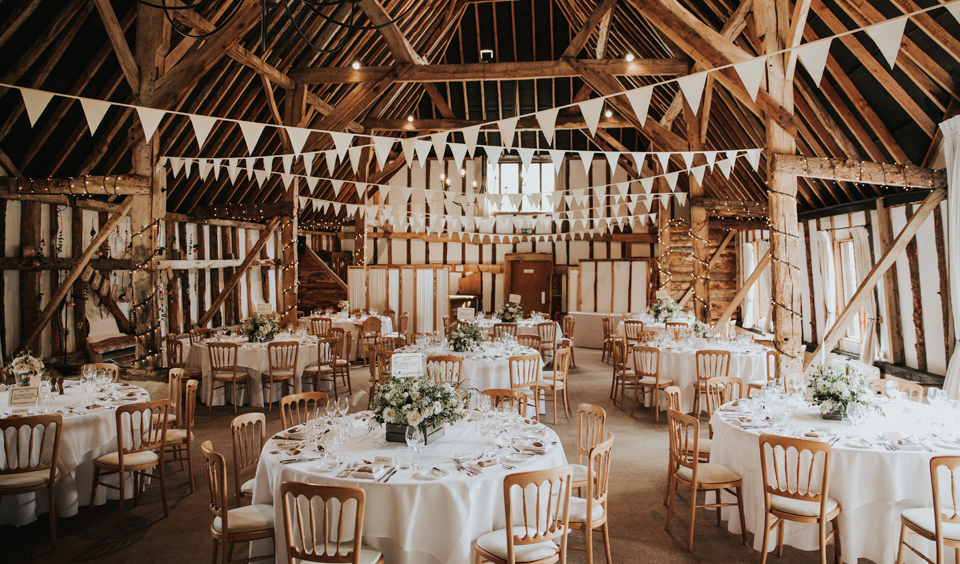 The rustic wedding barn is set up for the wedding breakfast at Clock Barn